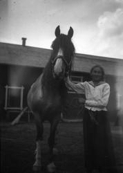 Flicka med häst utanför uthus.