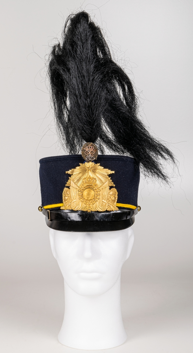 Mössa, uniformsmössa, blå med stor mässingsbricka, lilla riksvapnet omgivet av lejon, flaggor och med kungl. krona ovanför samt 5-uddig stjärna med strålar. Överst plymfäste med tagelplym. M/1899.