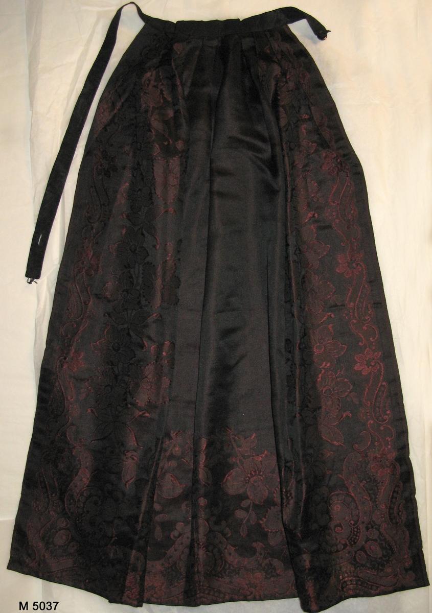 Förkläde i silke med varp/inslag i svart/rött med blombård runt kanter.  Linning av svart ripsband med knapp och hank.