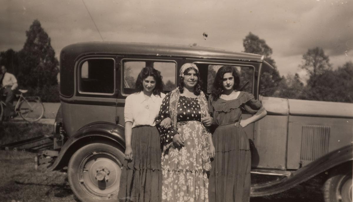 Tre romska kvinnor framför en bil i Sandviken under sommaren 1947. I bakgrunden syns en man lutad mot sin cykel.