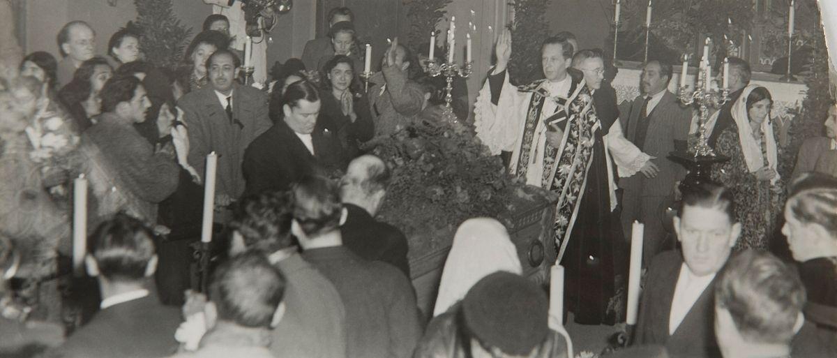 """Bilden är tagen i samband med begravningen av Johan Dimitri Taikon år 1950. Johan Dimitri Taikon hade under sin livstid en framstående roll bland svenska romer. Han föddes i slutet av 1870-talet och var en tidig förespråkare för romers rättigheter i Sverige. Redan 1933 skrev Johan Dimitri Taikon till skolöverstyrelsen och bad om skolundervisning för romska barn. Först tio år senare, efter flera avslag, blev han hörsammad. Tillsammans med den frikyrkligt engagerade Otto Sundberg, även kallad Riga Lajos, blev han beviljad 1500 kronor för att starta en """"försöksskola"""" vid lägret i Lilla Sköndal, Gubbängen i Stockholm. På 1940-talet var Dimitri Taikon även informant åt Nordiska museets intendent folklivsforskare Carl-Herman Tillhagen."""