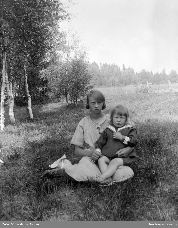 Porträtt på okänd ung flicka med ett litet barn i sitt knä.