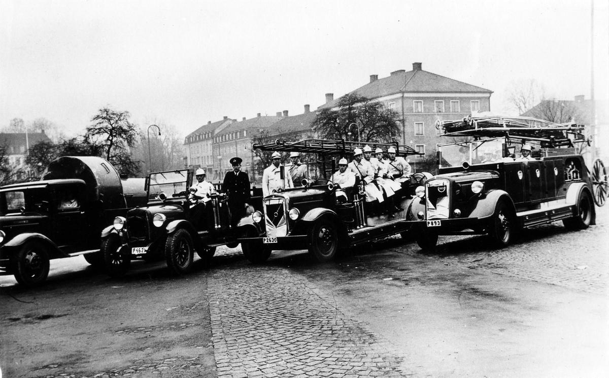 """Brandkåren på Stora torget med fyra brandbilar: Från vänster: P4621 Chevrolet 1927, P2630 Volvo 1936 (kallad """"2:an""""), P893 1940 (1939), P893 1921 """"Tidaholm"""", samma nr hade den första brandbilen som levererades omkring 15/4 1921.."""
