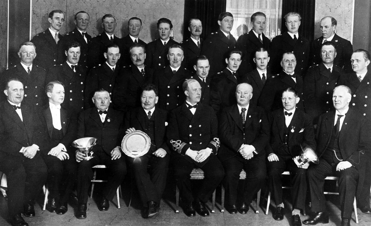Gruppbild av män tillhörande brandstyrelse och brandkår. Tre av männen på främsta raden håller i silverföremål.