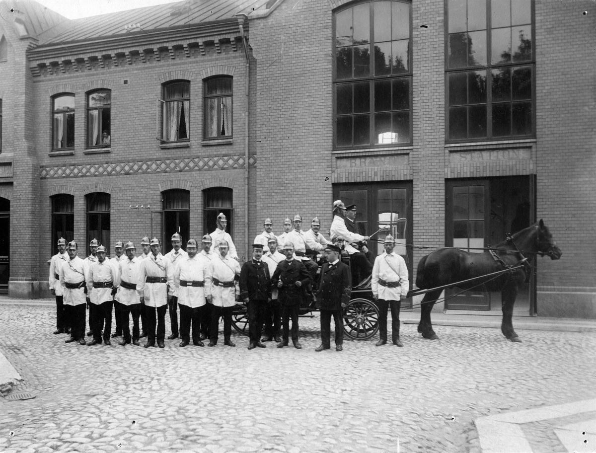 Framför brandstationen i kv. Kristina står ett antal uniformerade brandmän. Några sitter även på en redskapsvagn dragen av en häst. Vagnen köptes in 1913 och på kuskbocken sitter brandchef John Hj. Möller. I brandstationens ena fönster syns en person titta ut.