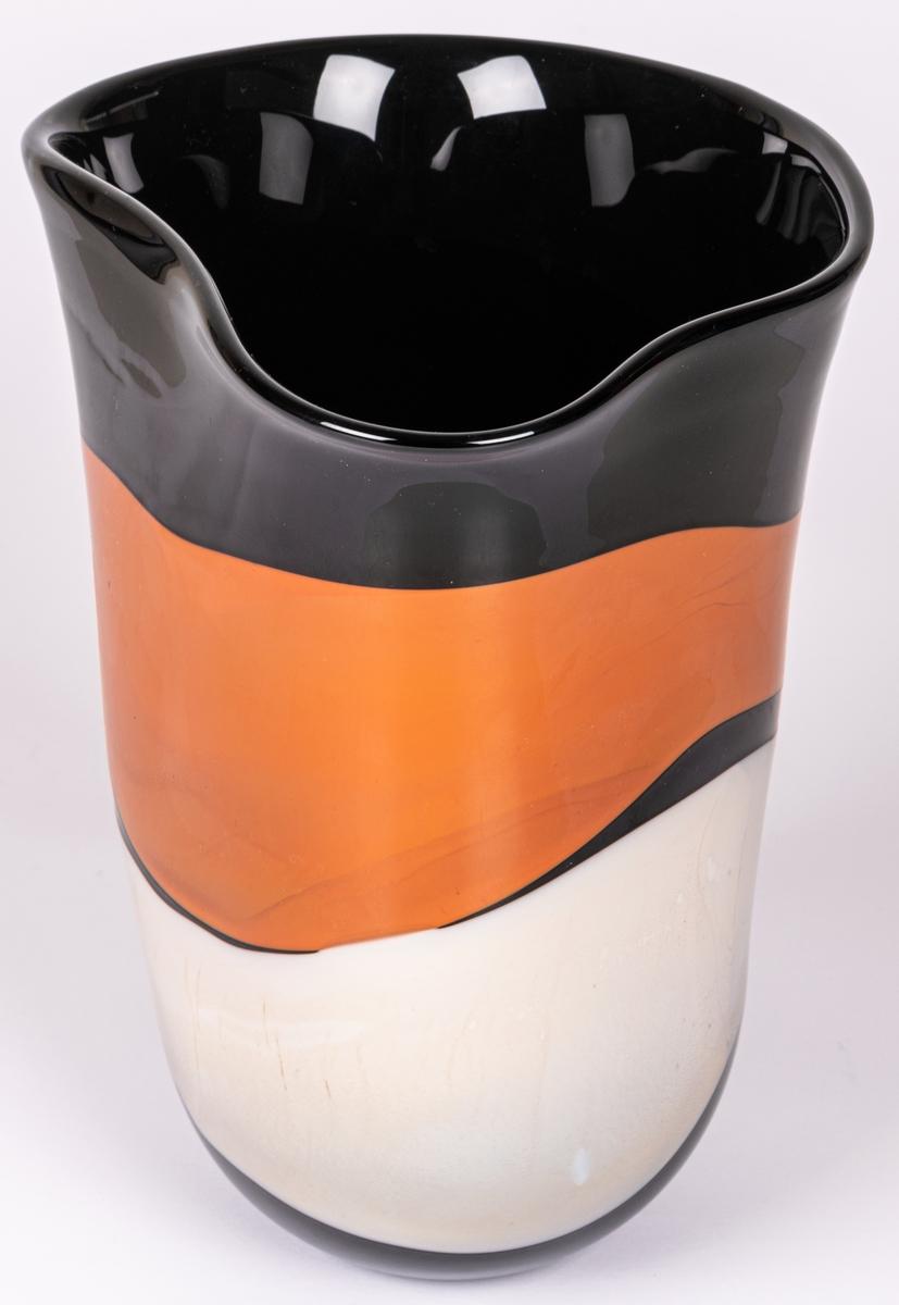 """Vas, blåst, med pålagda färgfält, modell """"Mali"""". Oregelbundet oval. Tvärrandig i svart, vitt och ljusbrunt i breda fält. Märkt under: """"Utställning""""."""