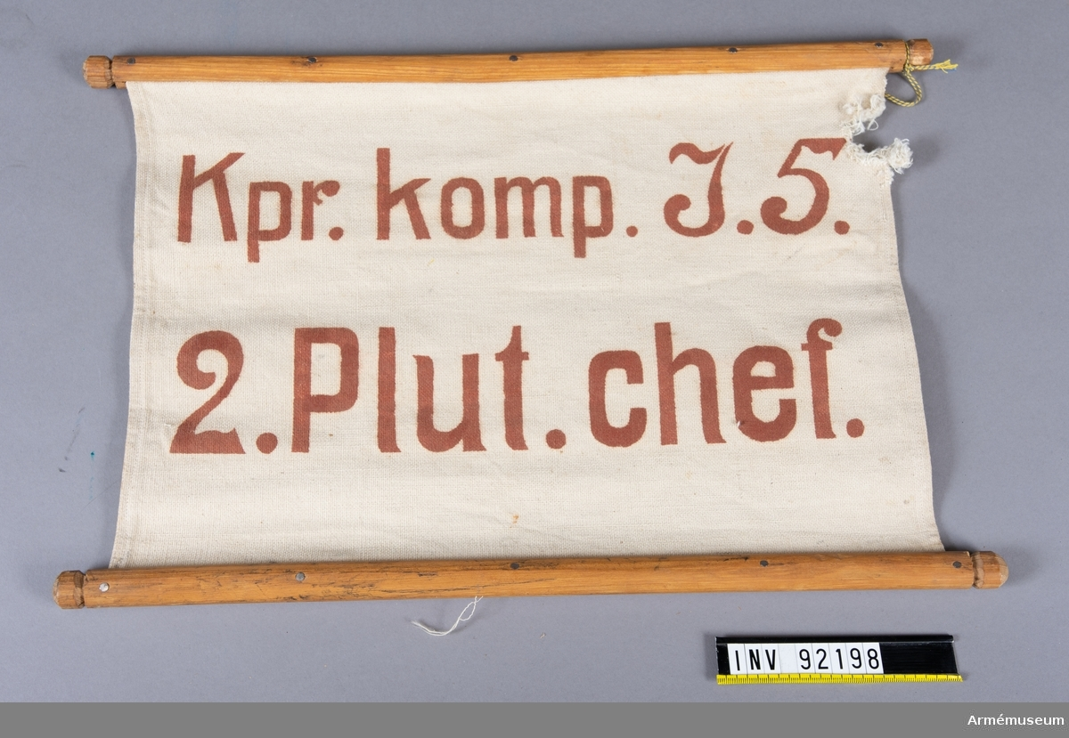 """Skylt av tyg av smärtingtyp fästa i träpinnar på långsidorna. Röd text: """"Kpr. komp. I.5. 2. Plut. chef."""""""