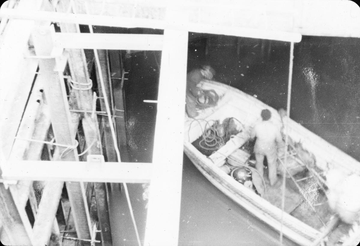 To menn i robåt, bergningsoppdrag.