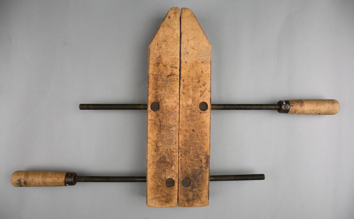 Tvinge.  Limtvinge i tre og med skruer av jern. Består av til sammen 4 deler. To like rektangulære tredeler med to hull, hvor ene ende er skråskjært. to skruestag ii jern med trehåndtak.
