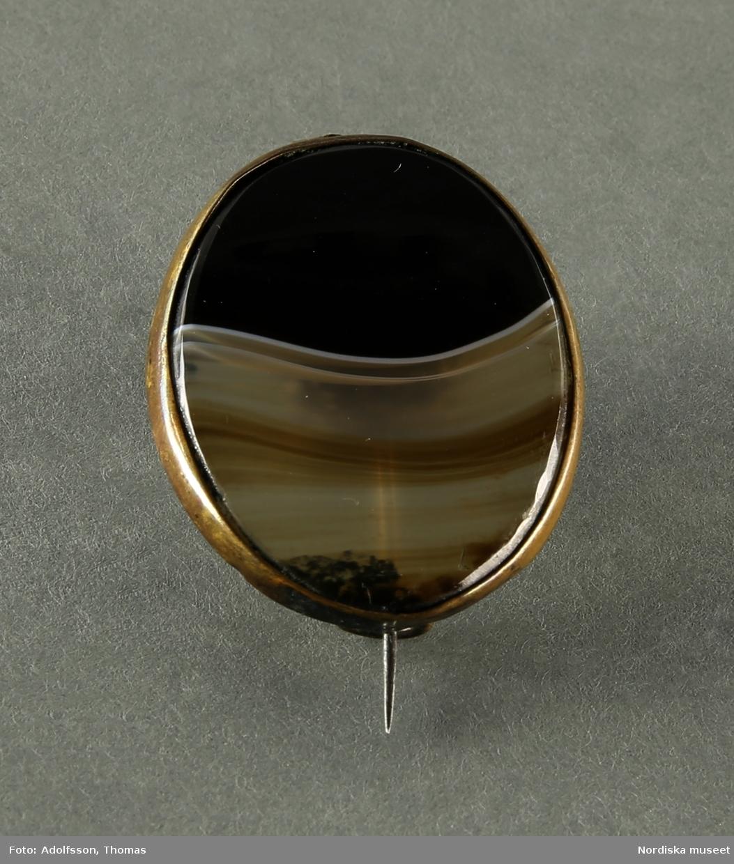 Brosch med ljusbrun, svart och vit plan oval agat, infattad i en tunn gulmetall ram.   /Cecilia Wallquist 2019-03-19