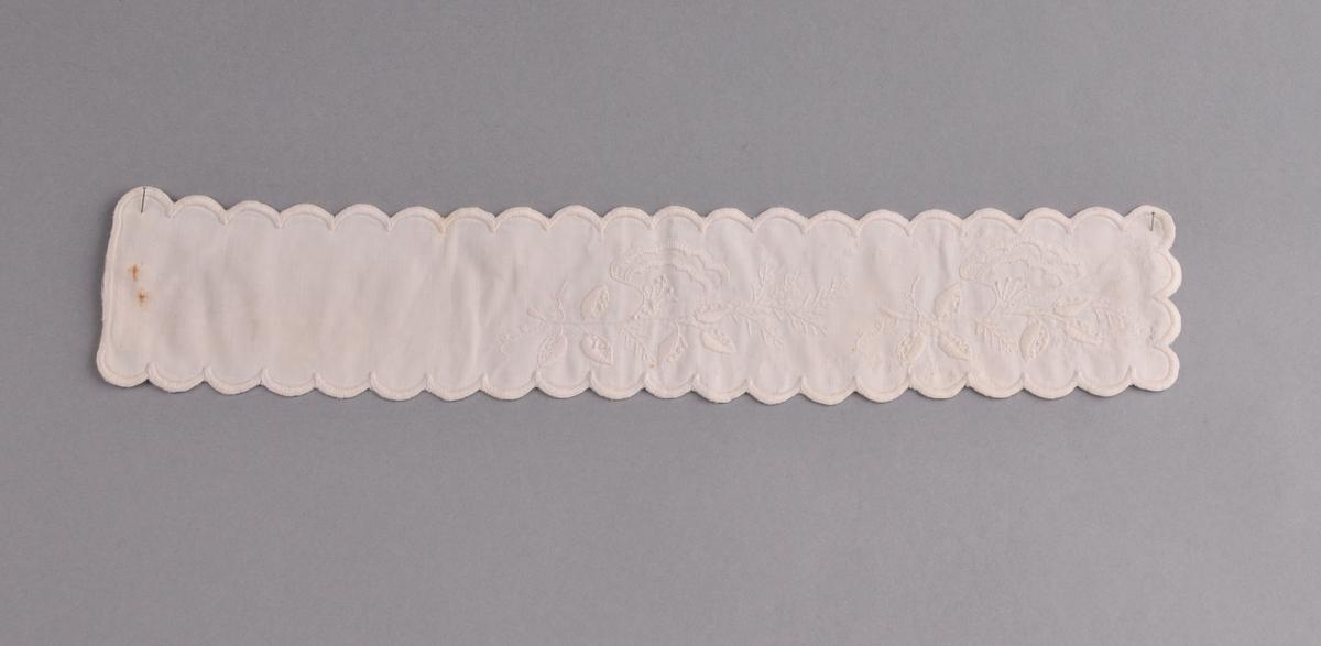 Kvitt band i bomull med rosesum i den eine enden. Kontursting,knutar, knappholssting, plattsum. Tungekant. Tøyet er lagt dobbelt og det er sauma gjennom begge laga.