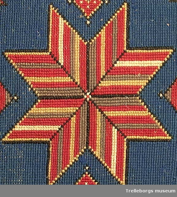 Spetsuddig stjärna i rött, gult, grönt med gul och brun kontur.  Blå botten, små stjärnor och hjärtan i rött och grönt.  Bård 6 cm bred, rött ornament på grön botten.  Innekudde.
