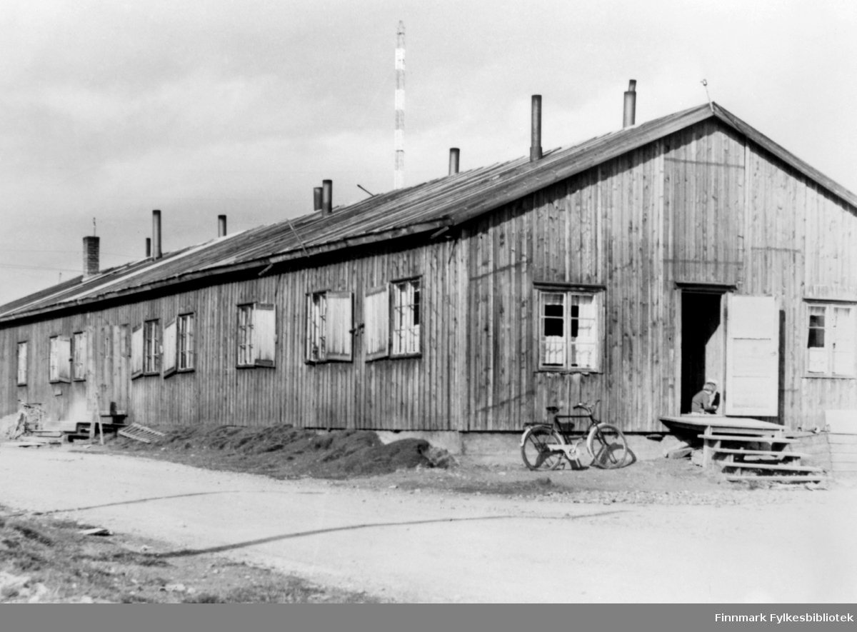 Bildet viser en boligbrakke i Vadsø fotografert en gang etter 1948. Ref. radiomastene som sto ferdige ca. 1948.