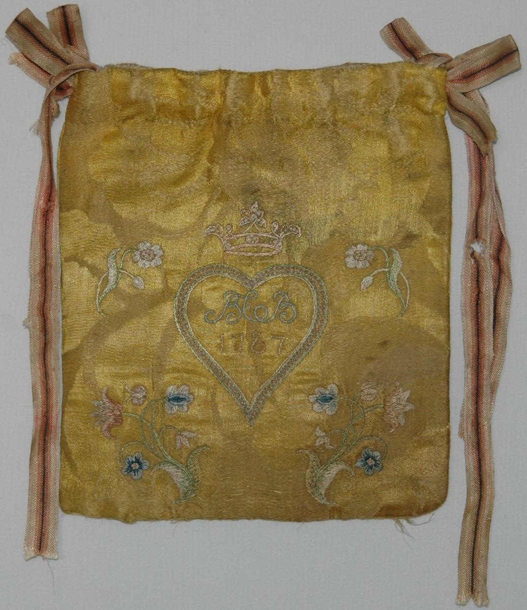 Handväska av gult sidendamasttyg med broderi i flera färer. Märkt på ena sidan BCB 1787 i ett hjärta under en grevlig krona. På andra sidan en broderad blomma. Fodrad med linnetyg.