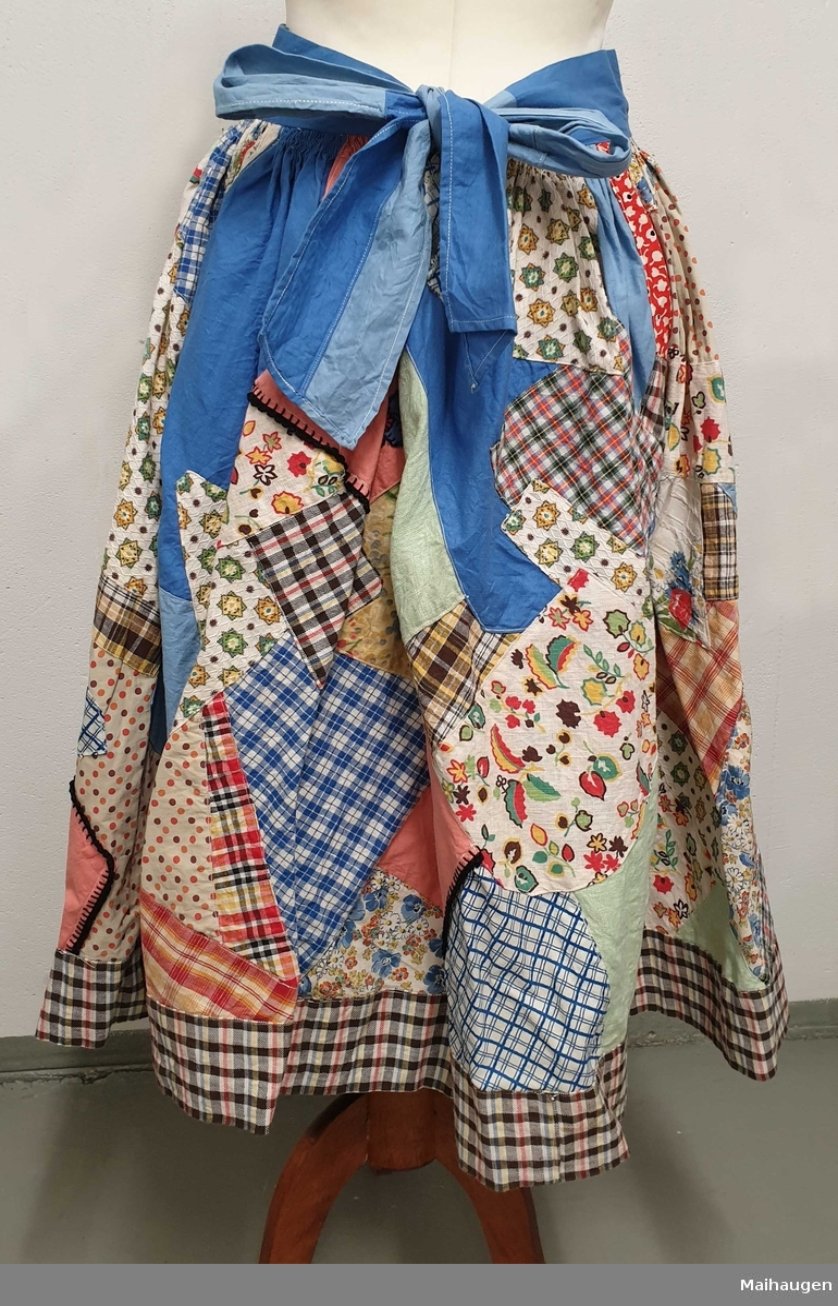 Sommerskjørt sydd sammen av bomullstoff med uilike mønstre. Blå linning som knytes på ryggen.