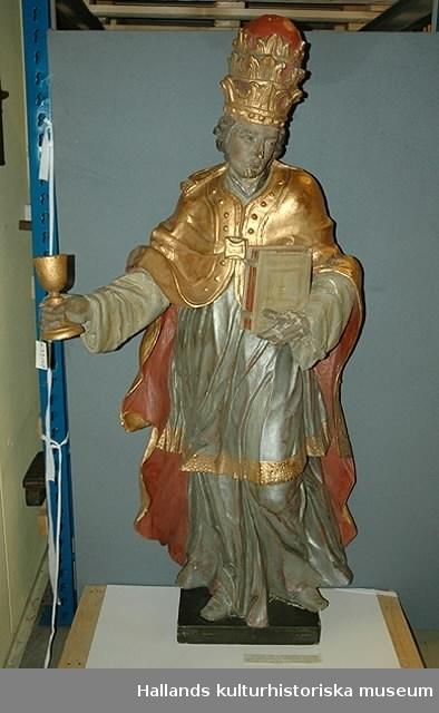 Friskulptur. Påvefigur. Attribut: tiara, bok och kalk. Sannolikt kyrkofadern Gregorius. Grå dräkt, kappa i gul färg, foder i rött.