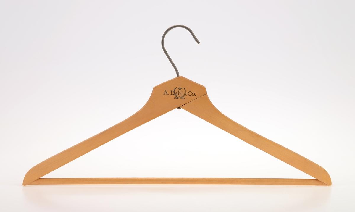 """En kleshenger i tre med to armer med stang i mellom slik at man kan henge klær på både armene og på stangen. For oppheng er det en enkel krok i metall. På den ene siden er det på trykt tekst, se """"Påført tekst/merker"""". Over hovedteksten er det en stjerne med bokstaver i. Under/i teksten er det to olivenkvister som holdes sammen med et bånd med tekst. For tekst se """"Påført tekst/merker""""."""