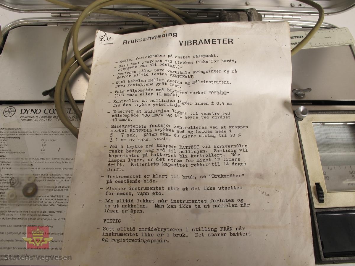 Sølvfarget koffert i aluminium med rystelsesmåler. Klistremerker med påskrifter på utsiden av kofferten Nitro Consult AB, FJELLSPRENGER DYNO Dyno Nobel, T.STANGELAND MASKIN A/S, 2353 OG 3147. Har plate med innskriften Nitro Consult AB STOCKHOLM PART NO 1111 SERIAL NO 1144 MADE IN SWEDEN. Oppi kofferten er det ledning, bruksanvisning på norsk, måleutstyr, og avleser med utskrift merket VS VIBTECH SENSOR AB som dekker måleområde fra 10 til 100 mm/s. Knapper for kontroll, batteritest og valg av måleområde. Klistremerke med påskriften DYNO CONSULT AS Vækerøvn. 8, Postboks 266 Skøyen, 0212 Oslo 2 Telefon: (02) 73 01 50 Telefax: (02) 73 01 50. Kontrollmerke som viser at måleren er kontrollert i juni 1989. Innskrift fra produsent VIBRAMETER 1111.