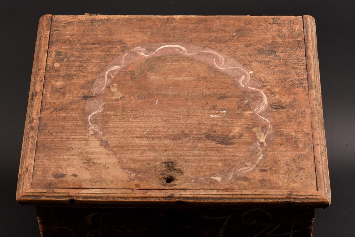 """Rektangulärt skrin med plant lock tillverkat av furu. Målat i brunt, med dekor på lockets ovansida, en målad krans i rött och vitt. På framsidan ditmålat årtal """"1794"""" i vitt. Beslag, spikar och gångjärn i järn. Nyckel saknas och ett gångjärn sitter löst."""