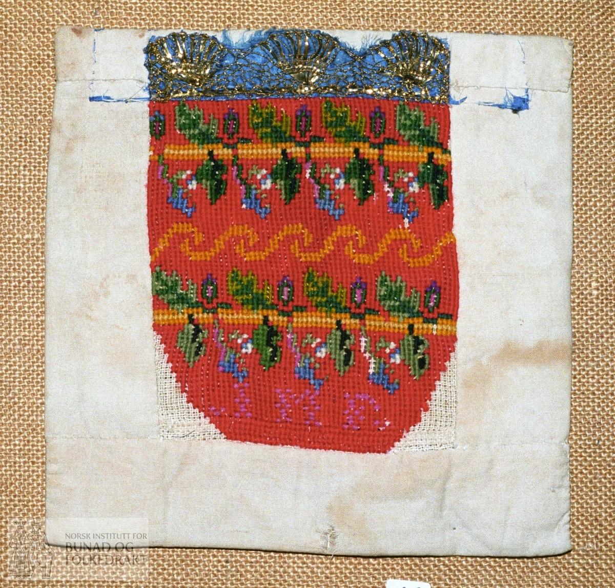 Matr.:  Stramei, korsstingssauma med mjukull i raudt med mønster i gule og grøne nyansar, blått, fiolett og litt kvitt. Kanta oppe med blå silke prydd med gullkniplingar. Bakside av ubleika bomullslerret, som er bretta over på framsida. Bokstavane A M D er sauma inn med fiolett.  Høgde broderi:         14 cm.  Breidde broderi:     12,5 cm. Breidde bandkanting:  2,6 cm.
