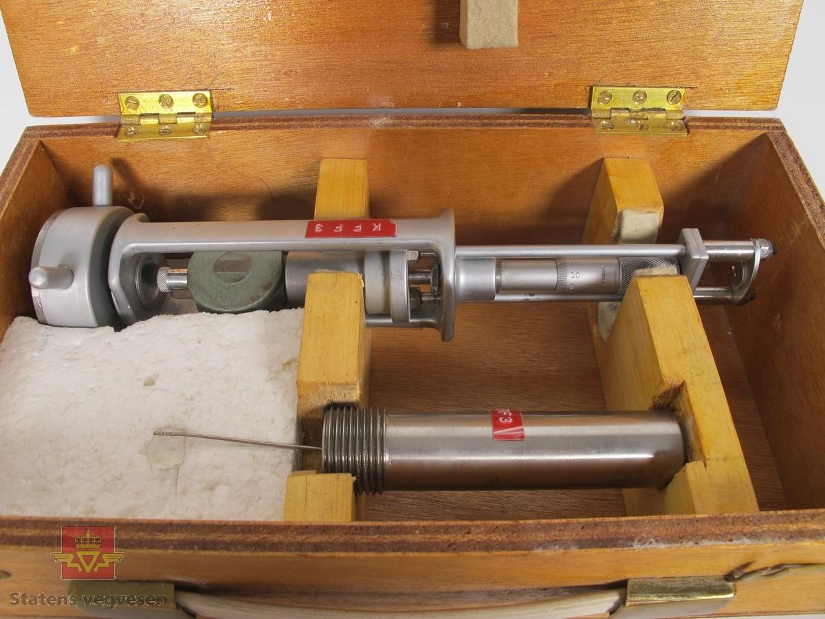 Oppbevaringskasse i treverk med bærehåndtak, som inneholder et måleinstrument i metall. Trekassen har klistremerke i blått med teksten HULL og en plate med påskriften DEPARTMENT OF MINING ENGINEERING, UNIVERSITY OF NEWCASTLE UPON TYNE. No. Type. MK1. Instrumentet har innskriften MOORE & WRIGHT. SHEFFIELD ENGLAND samt klistremerker med teksten KONTOR FOR FJELLSPRENGNINGSTEKNIKK FORSKNINGSVN. 3B - OSLO 3 - TLF.46 98 80, KFF3 og Nr.203. Måleinstrumentet består av to deler som skrus sammen ved måling. Ved siden av måleinstrumentet ligger en hvit lapp med påskriften: Kontrollert 29/11-68 og 14/3-69.