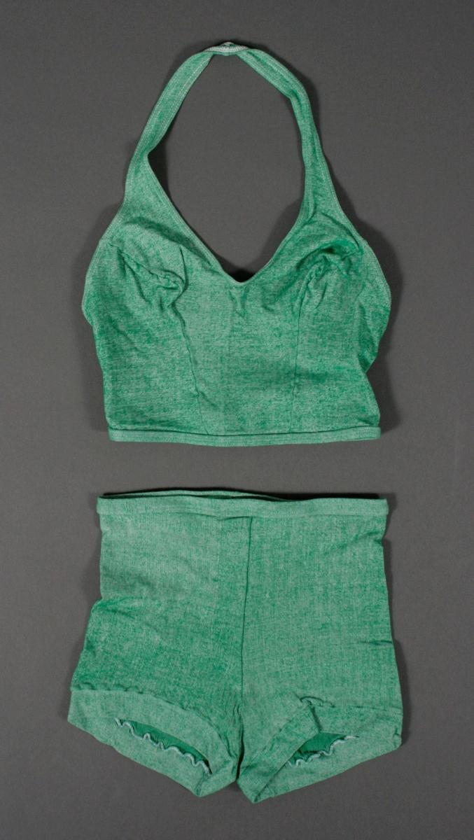 Todelt, overdel og bukse i grønnmelert jersystoff. Høy bukse med med imitert gylf foran og små bukseben. Strikk i livet. Overdelen har hel stropp rundt nakken. Strikk i nedre kant på overdelen. Fabrikkmerker isydd på innsiden av plaggdelene.
