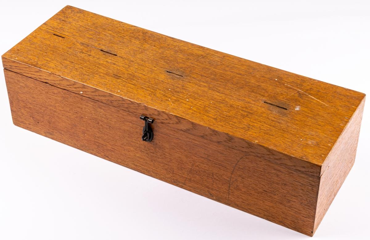 """Matpoletter av mässing förvarade i trälåda med 4 fack och inkast på locket. Lådan innehåller 989st av 4 typer. Text: """"SANDVIKENS MATSERVERING"""" och ett nummer på baksidan: """"C.C. SPORRONG 6 Co STOCKHOLM"""". Vidare finns 17 papperspoletter för arbetare vid """"Sandvikens jernverk"""" Akt. BOL. Frukost och kvälsvard 45öre vid metserveringen vid Karlshem. 1 papperspolett för matsäckssmörgåsar 3öre, använda 1916-1917. En kupong för kaffe 30 öre finns även. Mått lådan: L 50,5cm B 16,5cm, H13,5cm."""