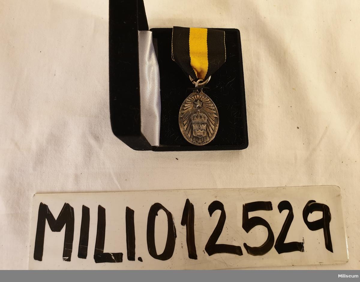 Hemvärnets förtjänstemedalj i valören silver, tillverkad av försilvrad mässing, med tillhörande bandspänne, extra ripsband och etui av svart plast.