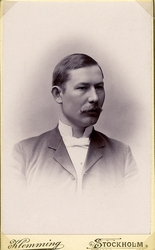 Foto av en man med mustascher, klädd i kavajkostym (?) med s