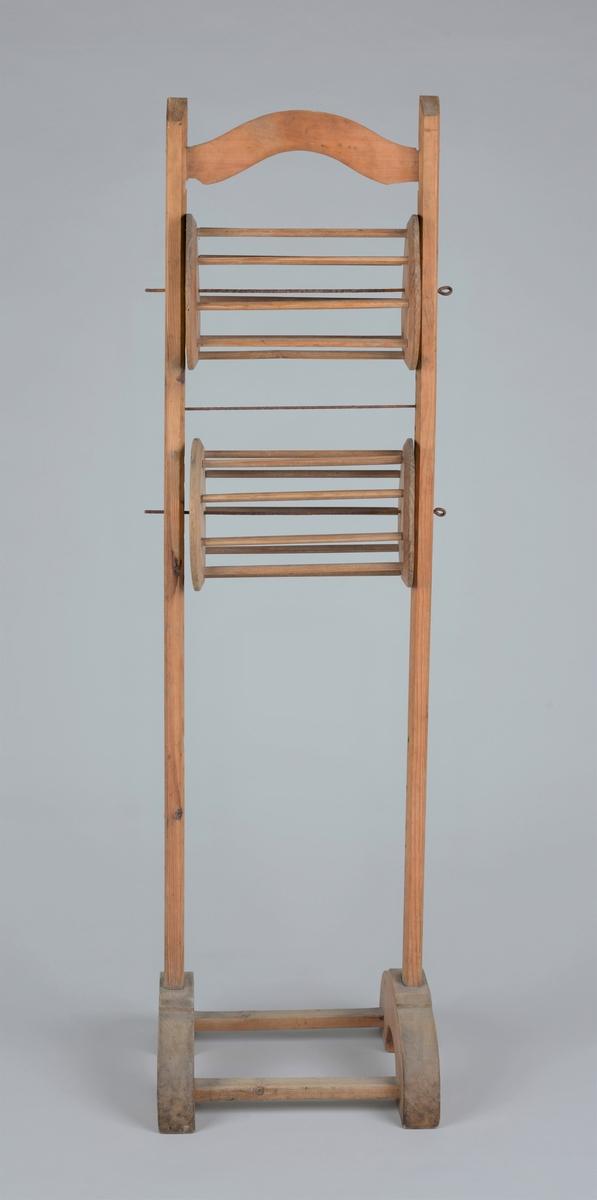 Høy garntvinne eller hespetre.  Stativ med to hjul for å vinne opp garnet til hesper eller nøster. Installasjon til behandling av garn fra hespe til nøste. Form: Tradisjonell men med buet under- og overdel