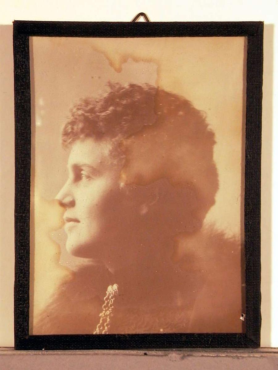 Portrettfotografi; brystbilde i venstreprofil, ung dame medkortklippet krusete hår, om skulderen henger et pelsstykke og fra halslinningen to knappesmykker. Fotografiet er overbelyst, og siden skadet ved brune skjolder.