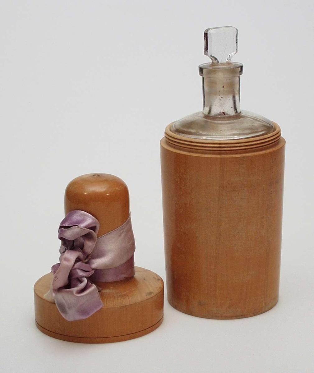 Rund parfymeflaske i pressglass med beholder i tre. Beholderen har skrulukking. Den er dekorert med et lilla silkebånd.