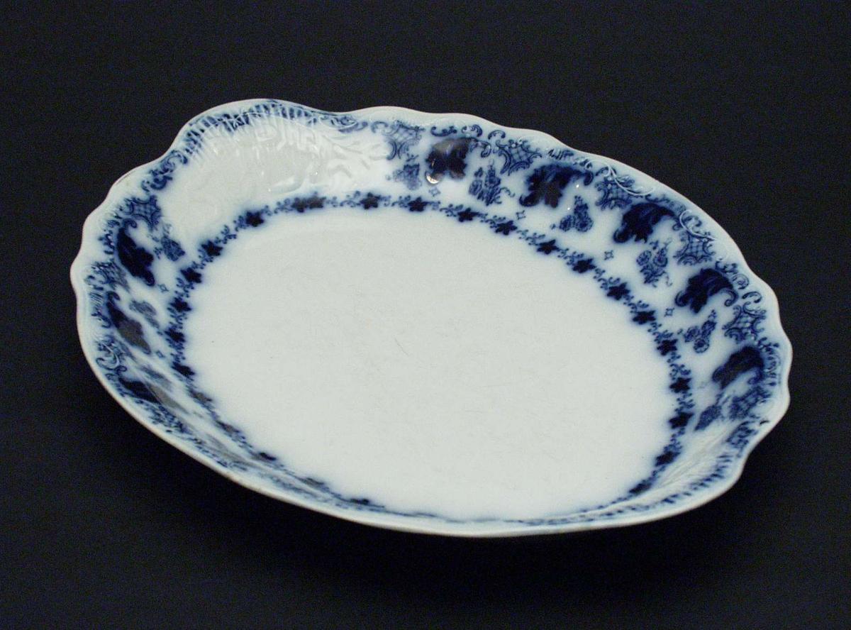 Ovalt fat i porselen med utoverbrettet tungekant. Fatet har blå dekor i form av blomster og bladverk. Dekor i godset.
