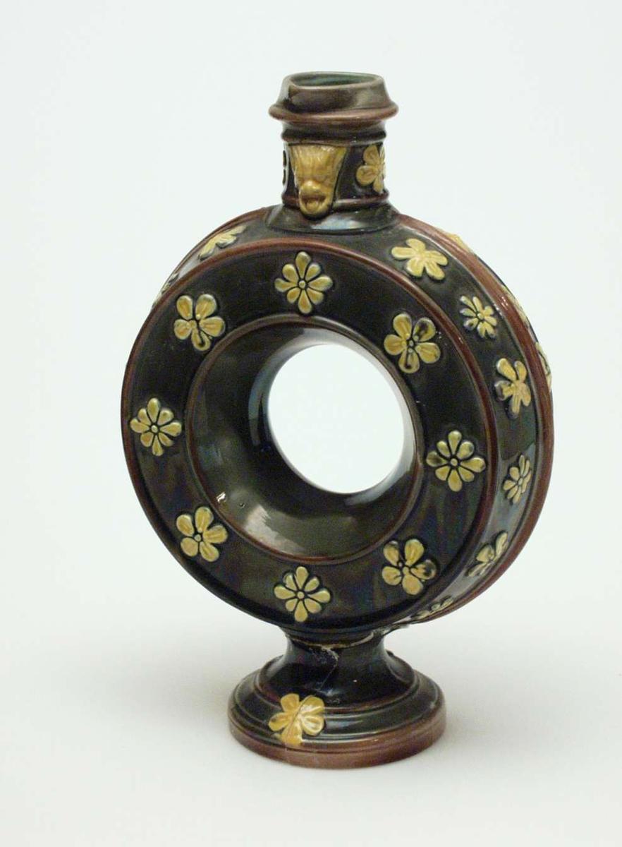 Grønn karaffel i keramikk med hull i midten. Den er dekorert med brune linjer og gule opphøyde blomster. Hanken er slått av.