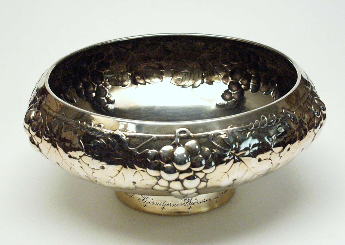 Kobber og gullforgylt bolle i sølv. Den er dekorert med bladranker og drueklaser. Uthamring langs kanten.