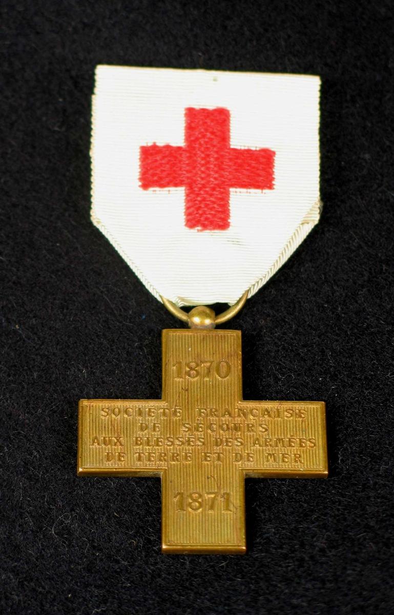 Medalje i messing (?) med hvitt bånd i silkerips og rødt kors. Korset er glatt på baksiden.