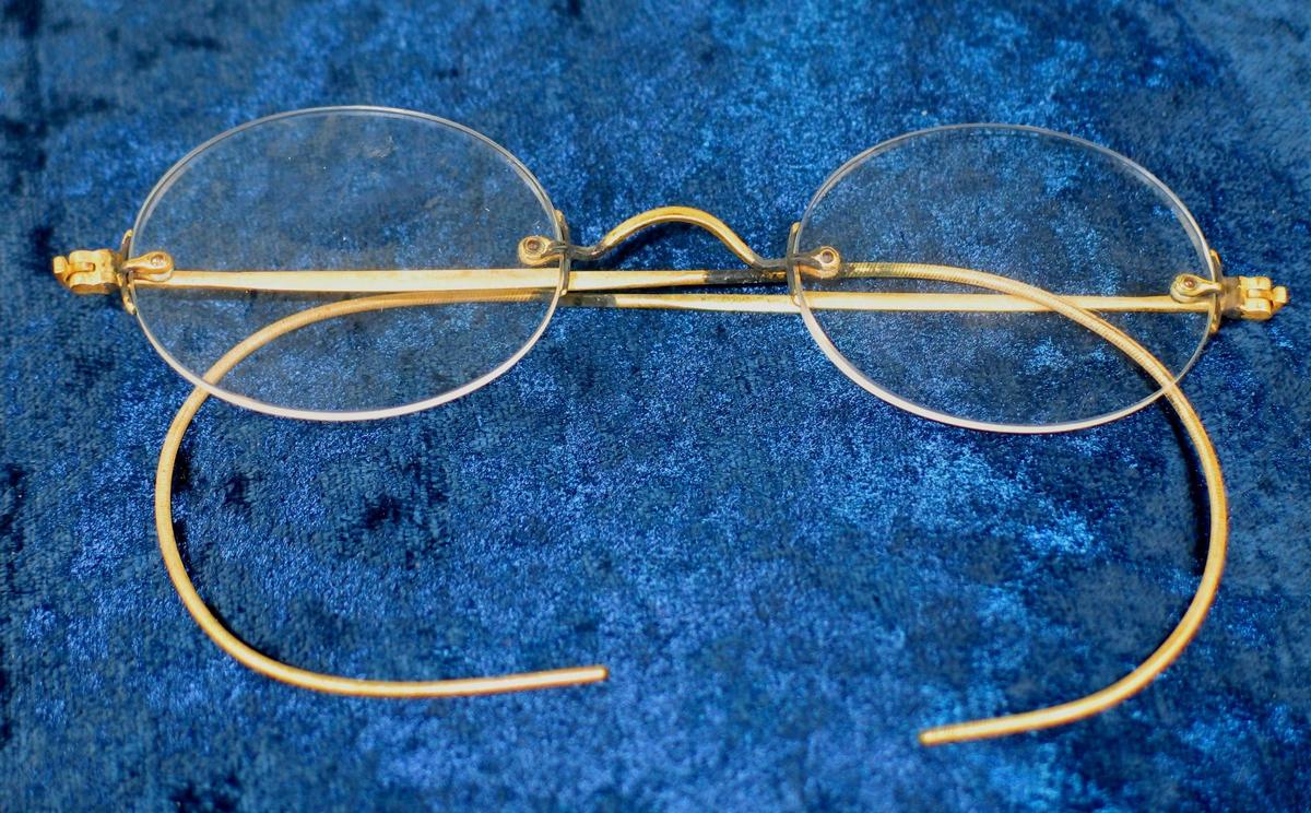 Brille i gyllent metall.