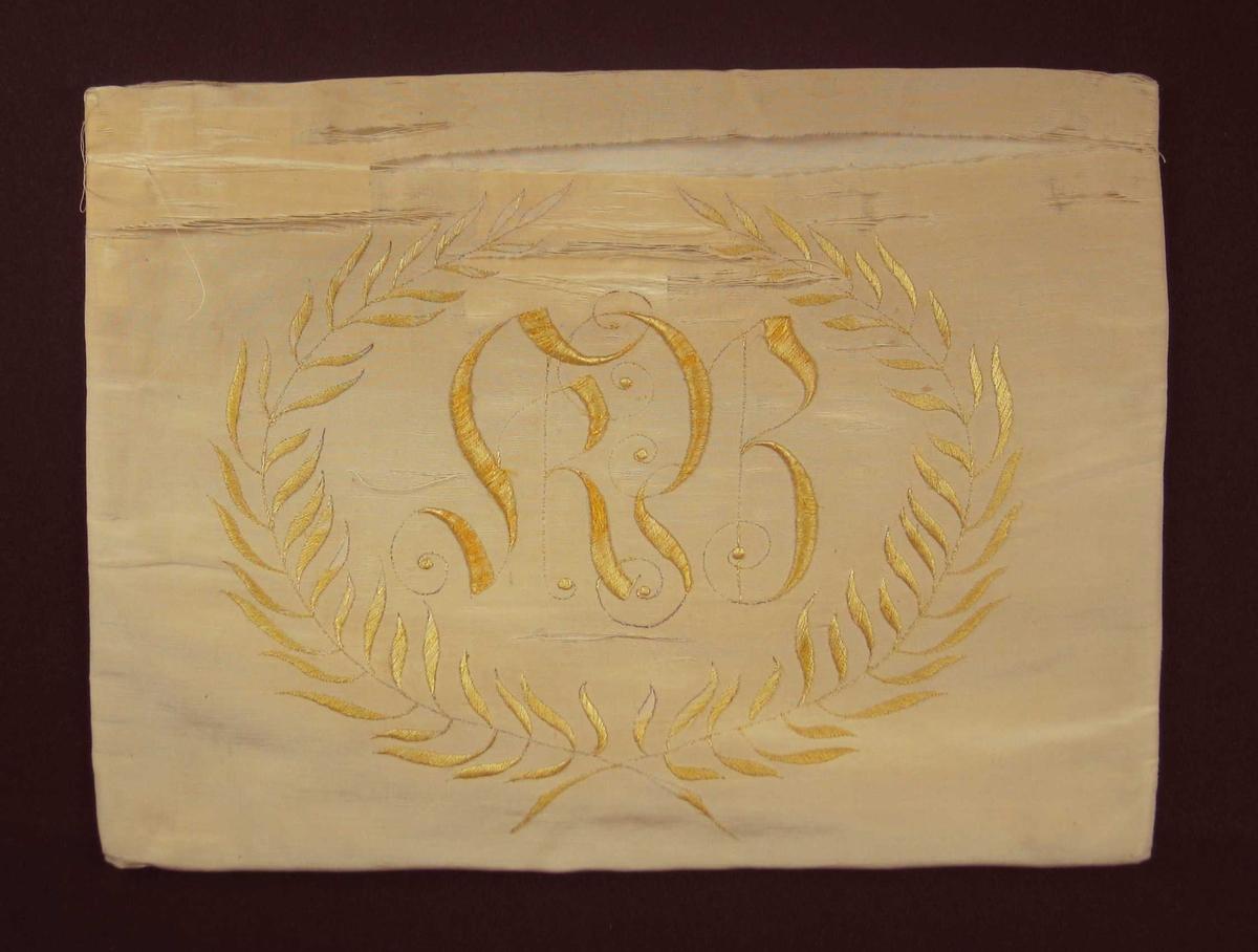 Gul silkepute med monogram innfattet i laurbærkrans. Puten er sammensydd i sidene og lukking bak med fem svarte trykknapper. De to laurbærgrenene er brodert med stilkesting og plattsøm. Monogrammet er brodert med stilkesting og tykksøm.