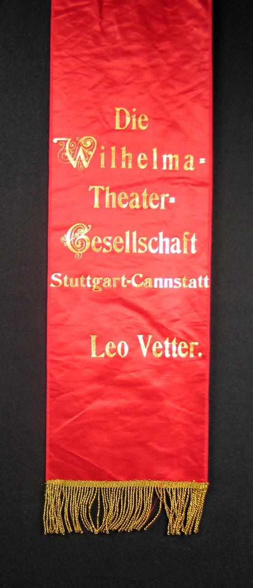 Begravelsessløyfe i rød silke med tekst og frynser i gull.
