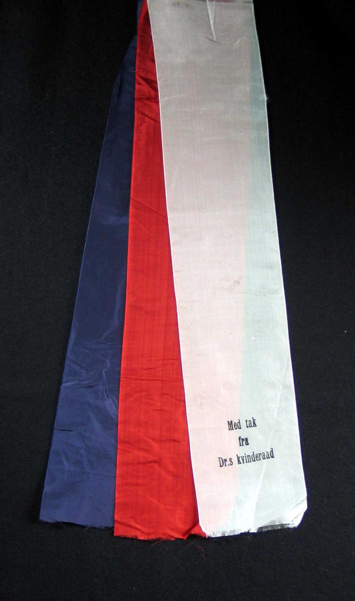 Begravelsessløyfe i rød, hvit og blå silke med svart tekst.