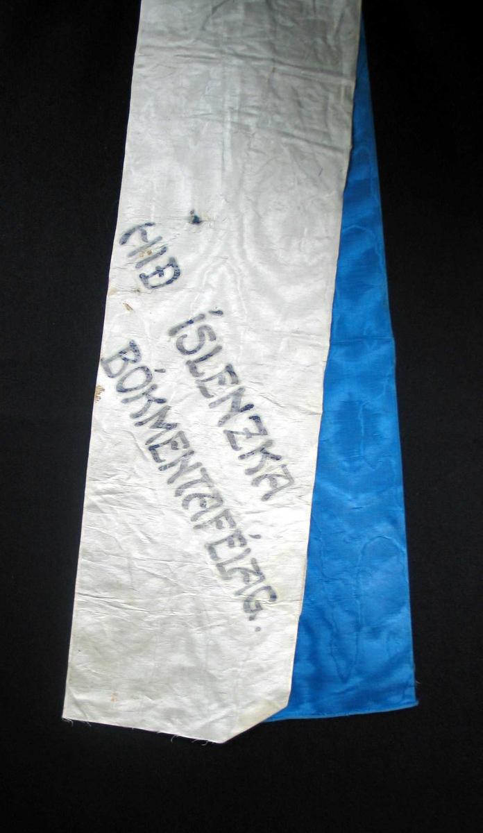 Begravelsessløyfe i hvit og blå silke med svart tekst.