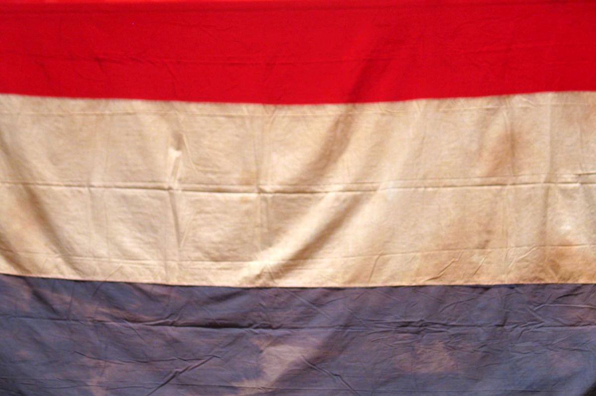 Nederlansk flagg med påsydd løpegang, snor og metallring.