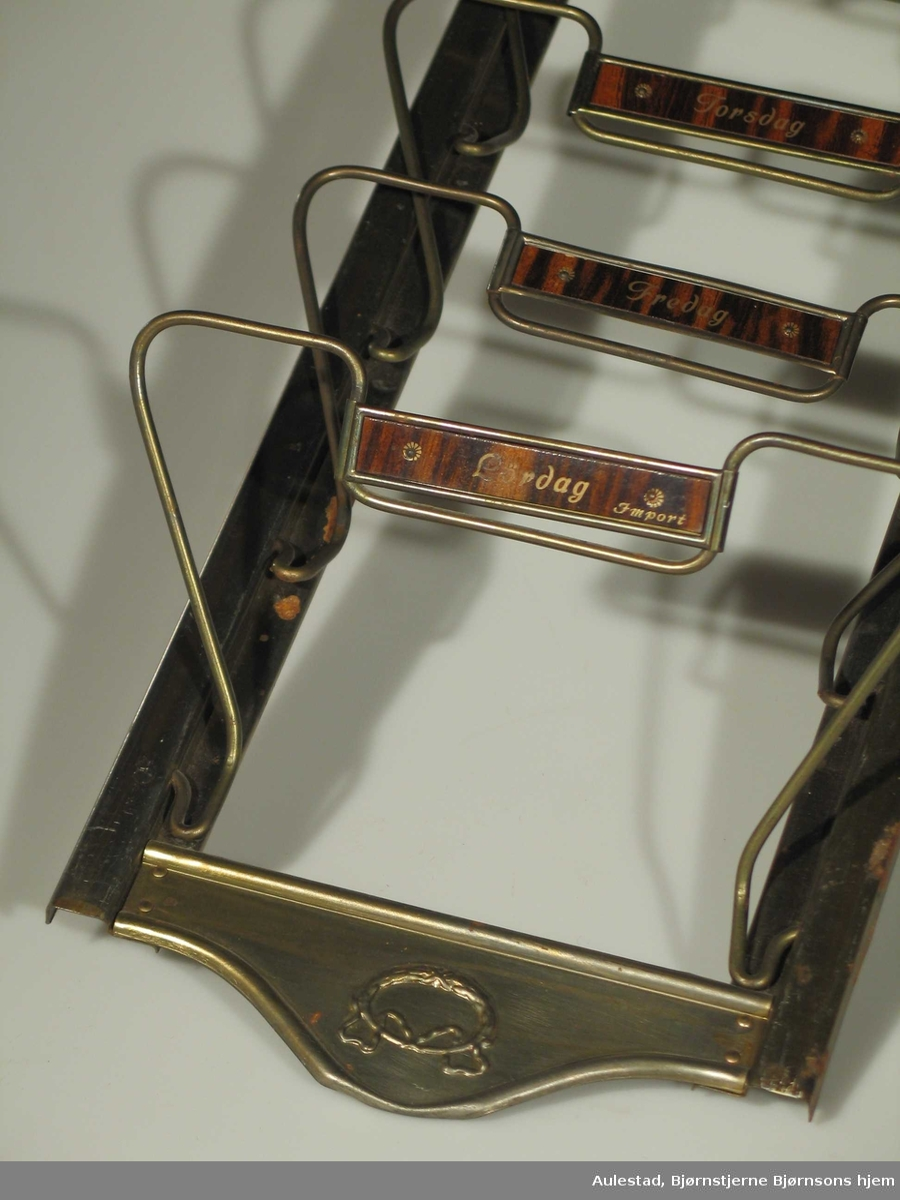 Avisholder i metall. Rektangulær ramme med klaffer i streng med malte ukedagsnavn. Eikemalt bakgrunn for navn. Presset laurbærguirlander.