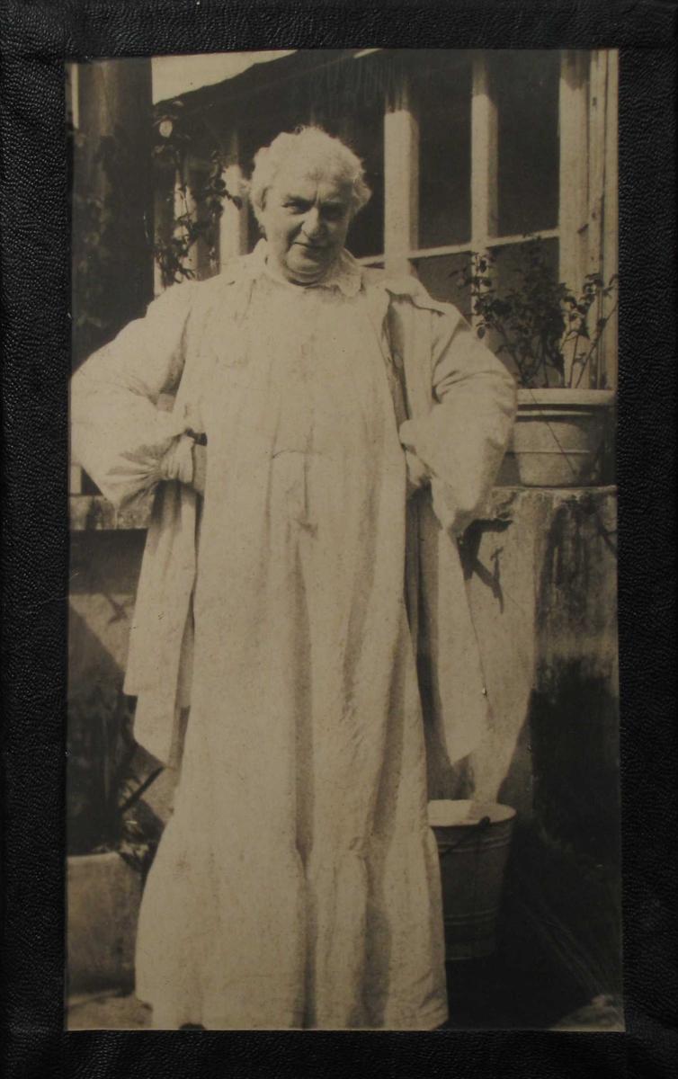 Eldre kvinne i hvit kjole foran et hus.