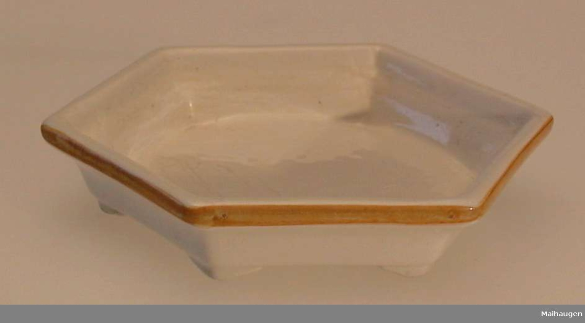 Sekskantet skål i keramikk med små bein i hvert hjørne.Gul stripe øverst.