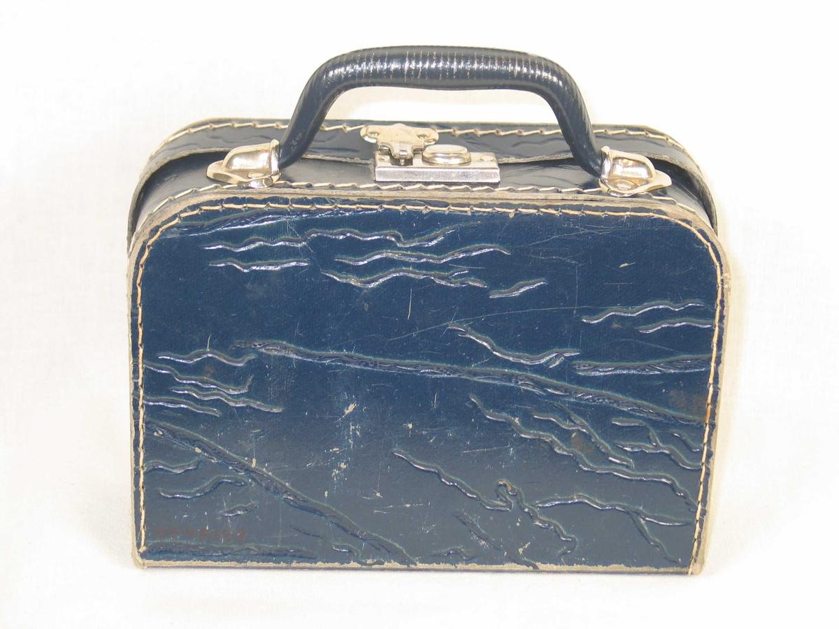 Blå dokkekoffert i blå papp. Kofferten inneholder fem dokkekleshengere.