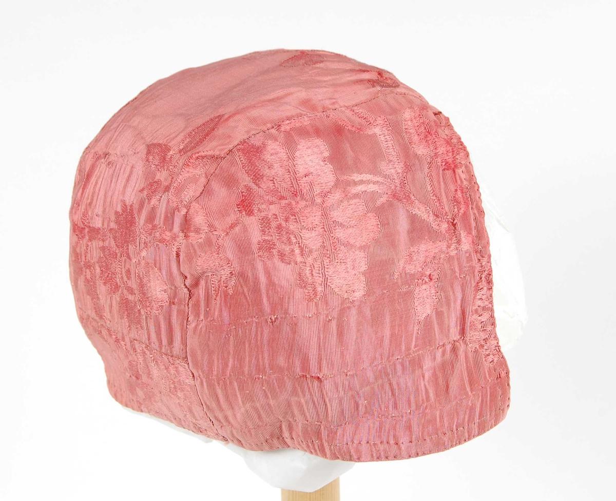 Rosa mønstervevet silkelue med fôr av bomull. Et stykke fra panne til nakke, et stykke som er avrundet mot midtstykket på hver side.
