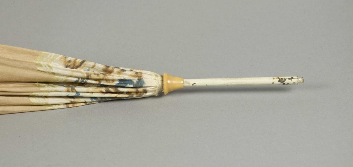 Parasoll av silke med trykt bord øverst og nederst. Spiler og stang/håndtak av metall. Avslutning på spilene: dreide bein- eller hornspiler, avslytning på håndtaket.: et skåret hestehode i bein eller tre.