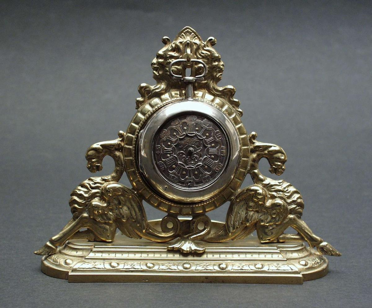 Lommeur av sølv hengt opp i et stativ av messing. Stativet er dekorert med to fabeldyr og to løvehoder. Uret mangler visere. I lokket er det et papir med uleselig håndskrift.