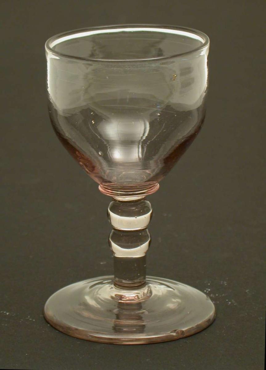 """Vinglass, dessert, med """"2de Knappe"""", dvs to skiver på stetten. Glasset er svakt sotfarvet med et lilla skjær. Glasset har små hakk i foten."""